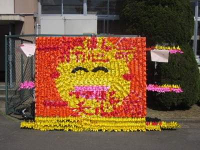 折り鶴を集めたデザイン「にこちゃんマーク」